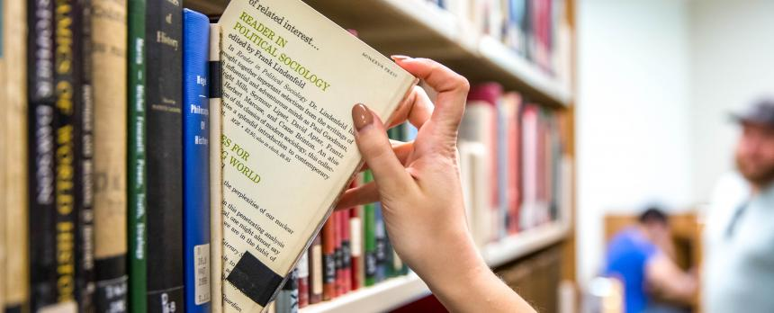 Image of a student picking a book from Library stack