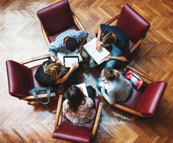 Image of students captured from above discussing seating on chairs